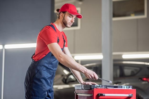 Détail assorti. concentrés intéressés jeune mécanicien automobile barbu avec détail de cueillette de clé près de tiroir en atelier