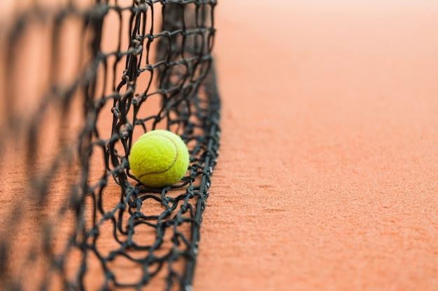 Détail d'une balle de tennis sur un filet noir