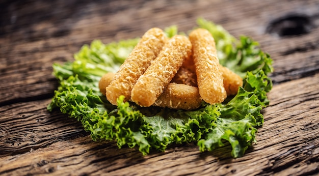 Détail de bâtonnets de mozzarela frits sur une feuille verte placée sur une table en bois rustique.