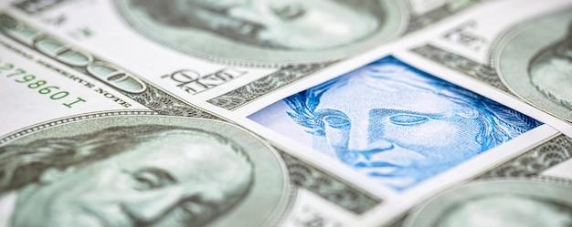 Détail d'un billet de cent reais du brésil, pris au piège entre des billets de 100 dollars américains