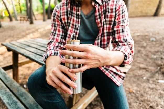 Détail d'une bouteille en aluminium dans les mains d'un homme à la campagne.