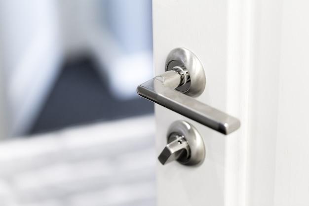 Détail d'un bouton métallique sur la porte blanche