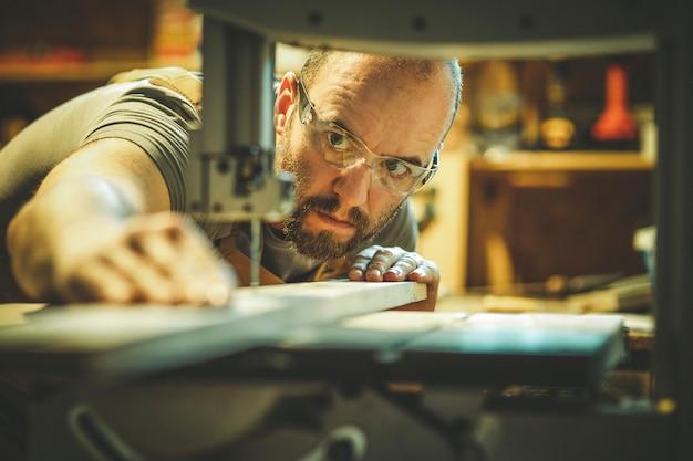 Détail d'un charpentier au travail coupant une planche avec une scie à ruban dans son atelier