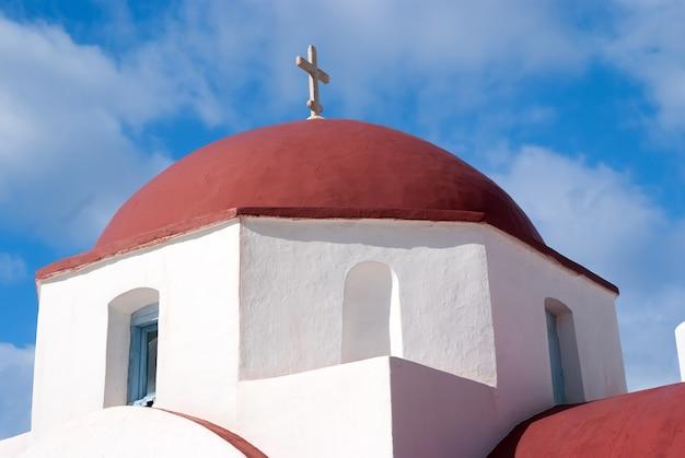 Détail de construction de l'église mykonos, grèce. chapelle avec croix sur coupole rouge, architecture. église agios nikolaos sur ciel ensoleillé. vacances d'été sur l'île méditerranéenne. wanderlust et concept de voyage.