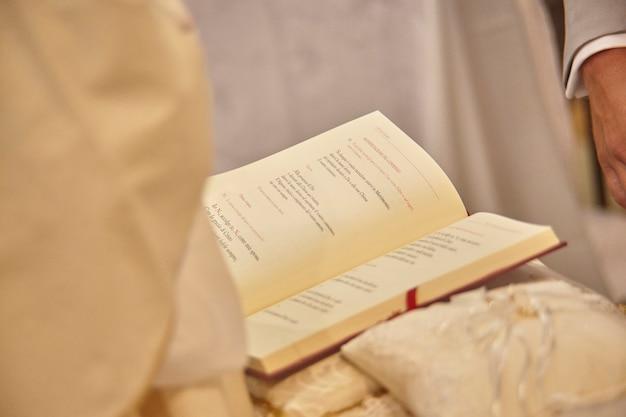 Détail d'une copie de l'évangile détenue par un prêtre lors du rite de la messe chrétienne catholique.