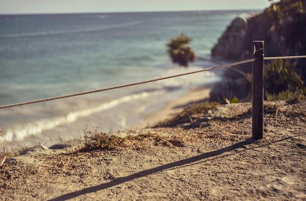 Détail d'une corde attachée à un poteau qui signale le danger du précipice sur la mer qui se trouve juste derrière.