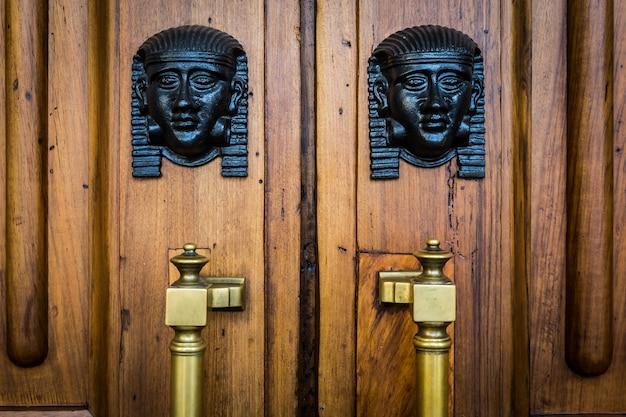 Détail de deux têtes de sphinx en bronze sur une vieille porte en bois - environ 100 ans, palais italien en italie du nord