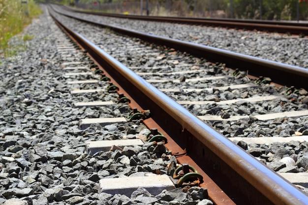 Détail du chemin de fer rouillé sur des pierres sombres