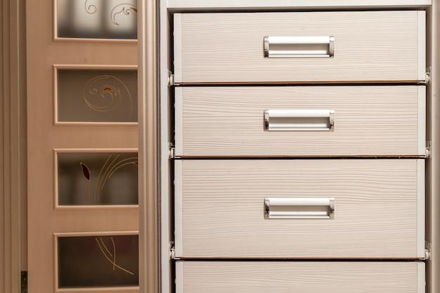 Détail du coffre de meuble en bois avec façade à tiroirs, poignées en métal, style vintage