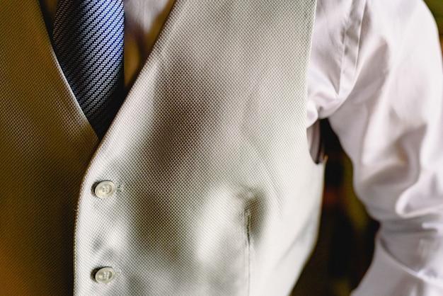 Détail du costume d'un homme élégamment vêtu d'une veste bleue.
