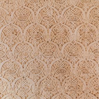 Détail du mur du site de l'unesco de l'alhambra à grenade - sud de l'espagne. caractères arabes vieux de 600 ans.