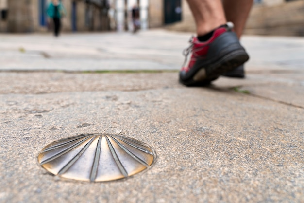 Détail du pied avec le soulier du pèlerin marchant le long du chemin de santiago - coquille de santiago.