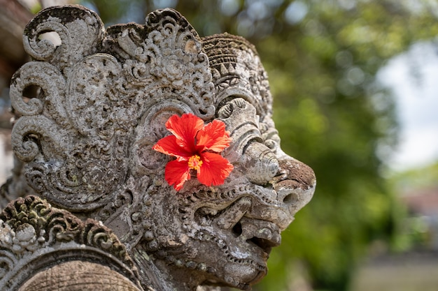 Détail du profil du haut d'une statue en pierre dans un temple hindou avec une fleur rouge