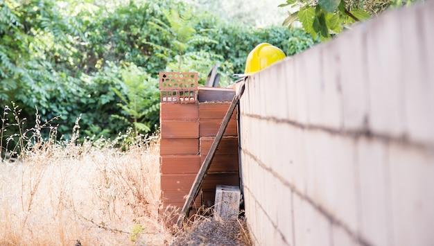 Détail du terrain à bâtir avec mur à moitié construit, briques et casque jaune