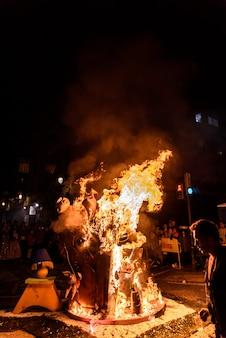 Détail d'une falla valenciana brûlant entre des flammes de feu.