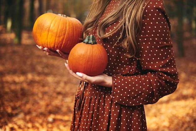 Détail d'une femme méconnaissable tenant des citrouilles dans la forêt d'automne