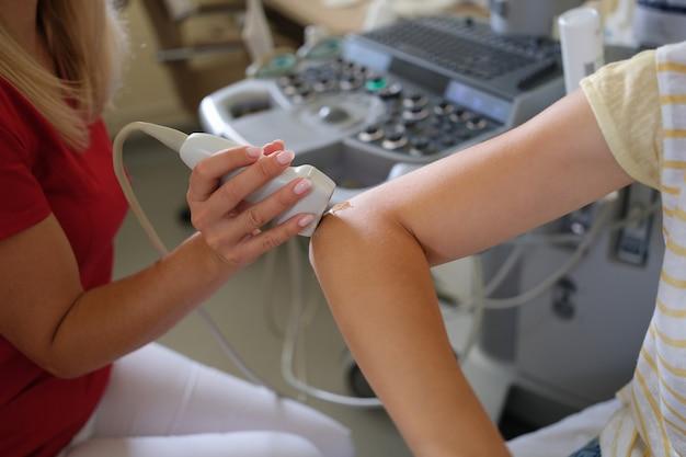Détail d'une femme utilisant une sonde à ultrasons sur le concept de recherche médicale de l'articulation du coude