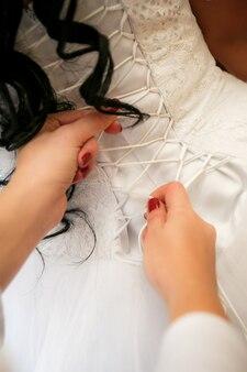 Détail de la fixation de la robe de la mariée lors de la préparation d'une cérémonie de mariage