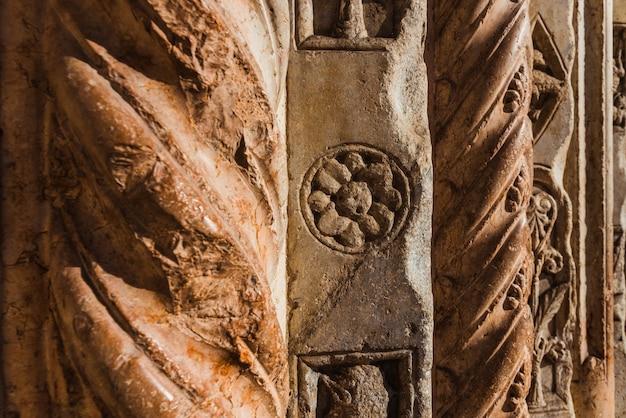 Détail des gravures dans la roche des colonnes du duomo de vérone, anciens symboles des artisans.