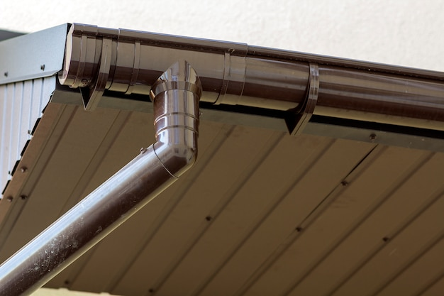 Détail en gros plan du coin de la maison de chalet avec revêtement en planches de métal brun et toit avec système de pluie de gouttière en acier. toiture, construction, installation de tuyaux de drainage et concept de raccordement.