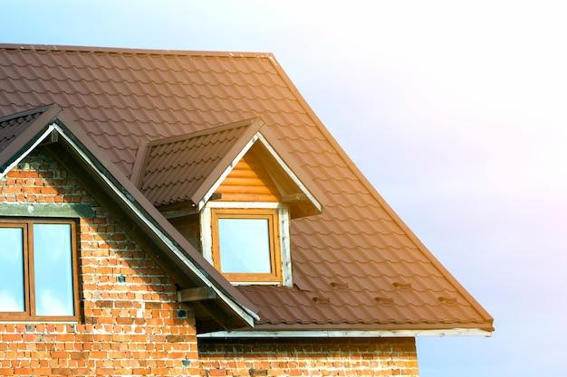 Détail en gros plan du nouveau dessus de maison en brique avec toit en bardeaux marron et lucarnes en plastique sur fond de ciel bleu clair. propriété immobilière et concept de travail réalisé par des professionnels.