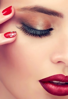 Le détail en gros plan du visage de la femme révèle des yeux fermés recouverts d'une paupière colorée dans un maquillage fumé, un sourcil bien formé et des lèvres rouge vif. maquillage, manucure et produits cosmétiques.