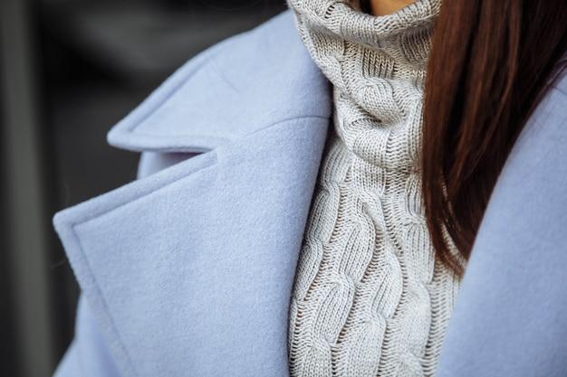 Détail gros plan des vêtements pour femmes. la fille dans un pull chaud et un manteau.