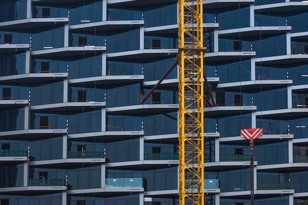 Détail d'une grue de construction dans le contexte de la façade en verre d'un beau gratte-ciel