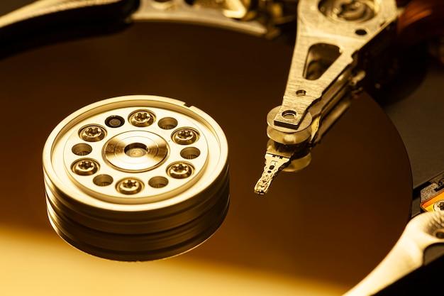 Détail de l'intérieur d'un disque dur avec la tête de lecture en fonctionnement, image de lumière rouge