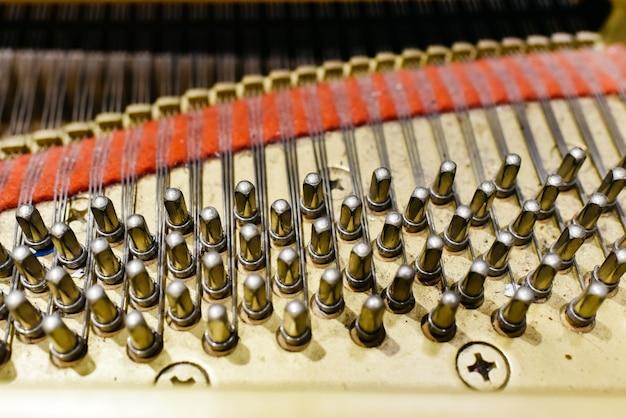 Détail de l'intérieur d'un piano avec la table d'harmonie, les ficelles et les cordes.