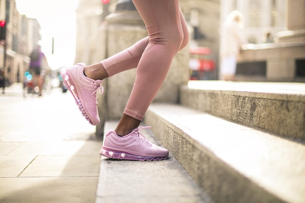 Détail des jambes de la femme en courant dans les escaliers dans la rue