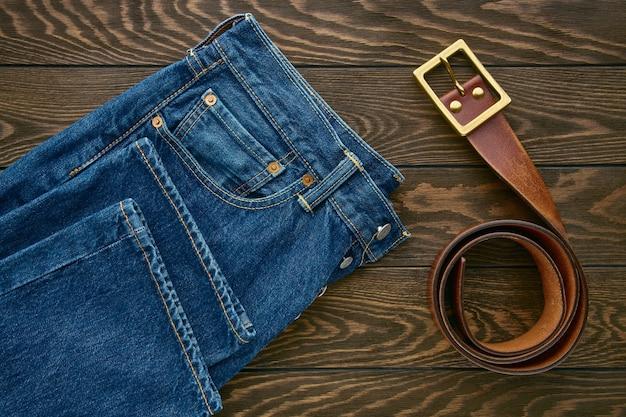 Détail De Jeans Pour Hommes Bleus Et Ceinture En Cuir Sur Surface En Bois Photo Premium