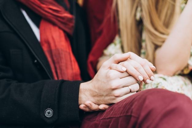Détail d'un jeune couple amoureux se tenant la main et assis dans le parc par une journée ensoleillée d'automne. mise au point sélective. notion de relations