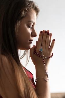 Détail d'une jeune fille priant le rosaire.