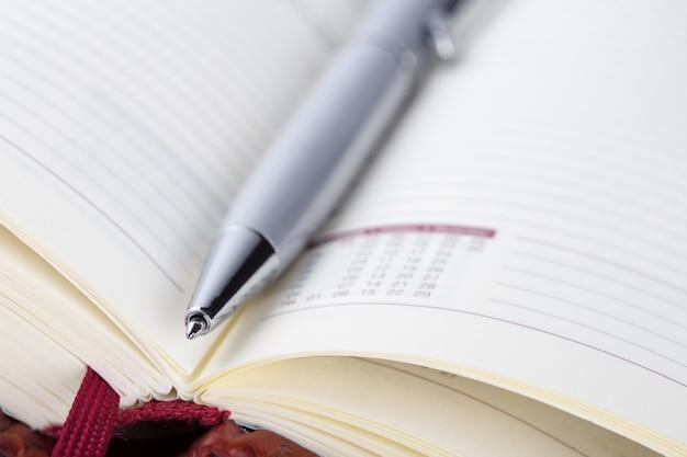 Détail d'un journal ouvert rouge avec un stylo