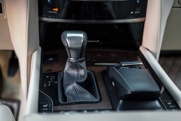 Détail d'un levier de vitesses automatique dans une nouvelle boîte de vitesses automatique en cuir noir de voiture moderne avec chrome