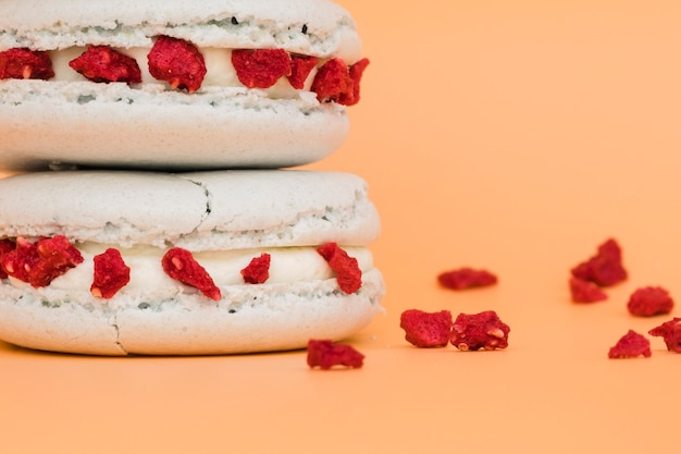 Détail de macaron blanc avec des baies rouges séchées sur fond coloré