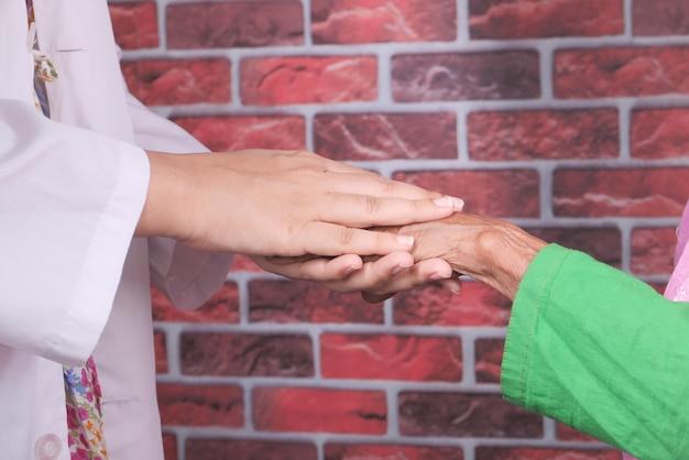 Détail de la main du médecin tenant la main des femmes âgées