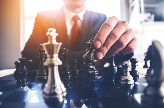 Détail d'une main effectuant le premier mouvement dans une partie d'échecs, déplaçant le pion d'un champ vers l'avant