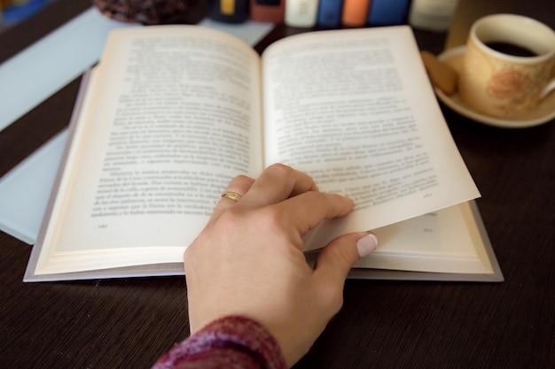 Détail de la main féminine en tournant une page du livre sur une table en bois sombre avec plus de livres et une tasse de café
