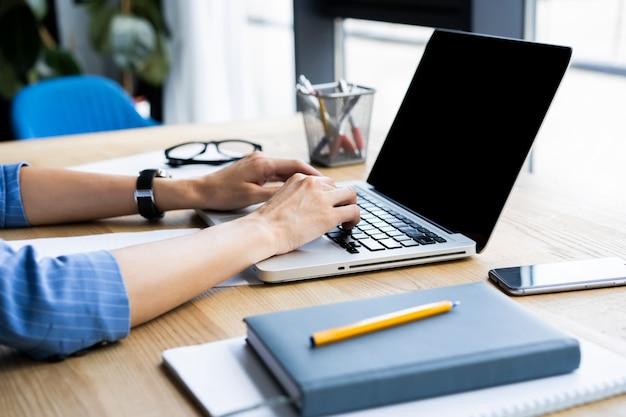 Détail de la main de la femme en tapant sur un clavier d'ordinateur portable.