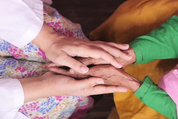 Détail de la main des femmes tenant la main des femmes âgées.
