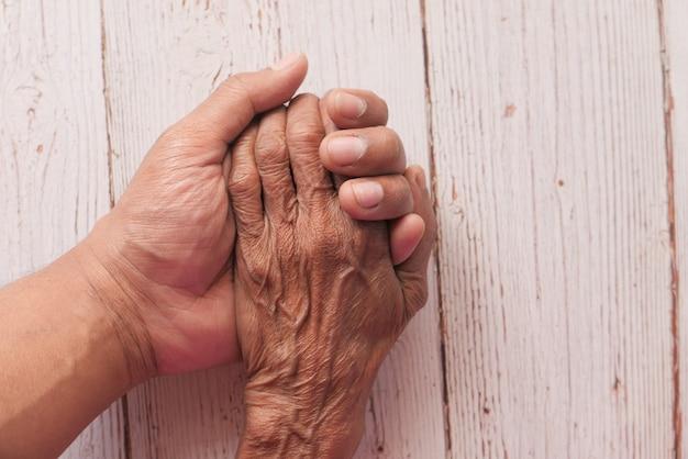 Détail de la main de l'homme main tenant la main des femmes âgées