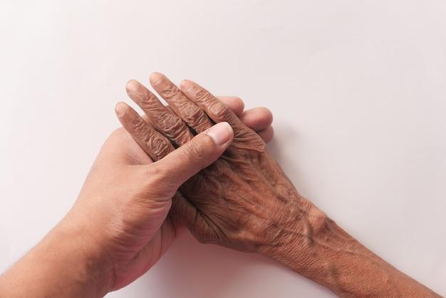 Détail de la main de l'homme tenant la main des femmes âgées.