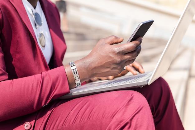 Détail de la main d'un homme utilisant un téléphone et un ordinateur