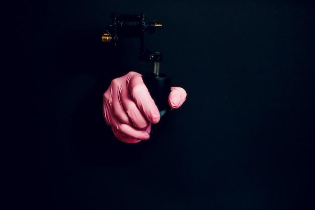 Détail de la main avec machine à tatouer rotative