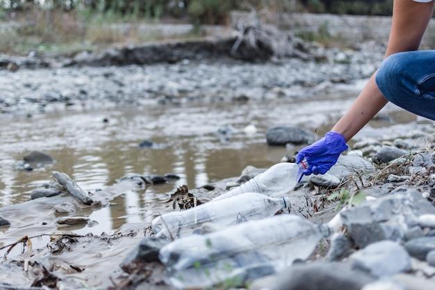 Détail d'une main ramassant une bouteille en plastique dans la rivière