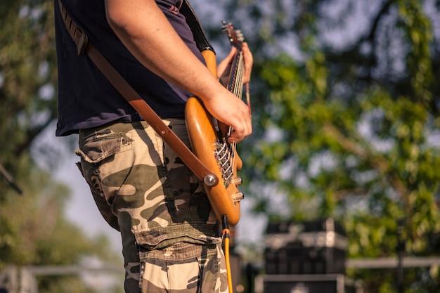 Détail de la main tout en jouant une basse acoustique en bois lors d'un concert de rock