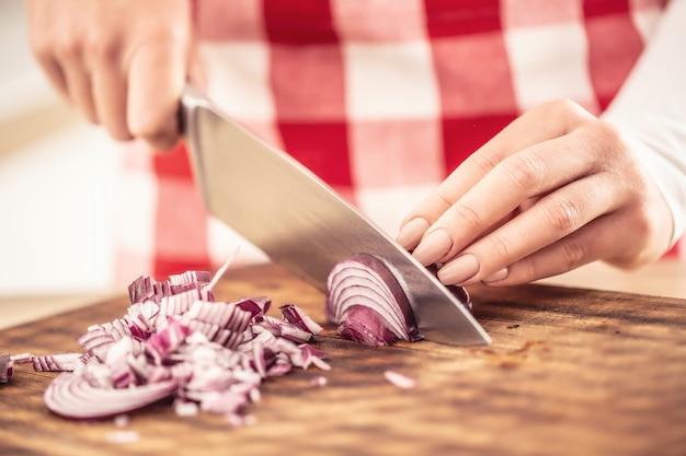 Détail de mains féminines coupant un oignon rouge sur une planche à découper.