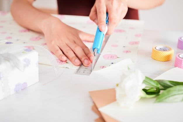 Détail des mains de femme emballant des cadeaux avec du papier cadeau